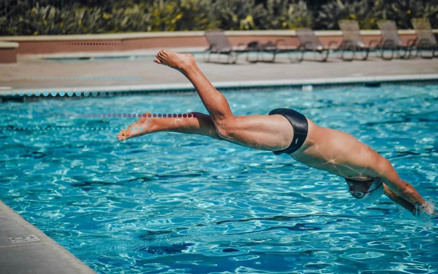 Chico tirándose de cabeza a la piscina